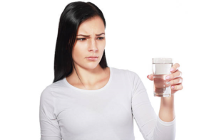 Women looking at glass of water - water smells like sulfur
